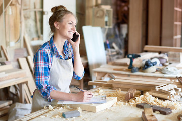 Portrait of modern young woman speaking by phone with client smiling and making notes in woodworking shop Wall mural