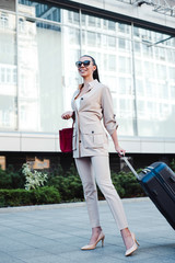 Business trip. Full length of beautiful young woman in sunglasses looking away with smile while pulling her luggage outdoors.