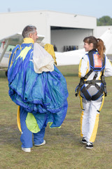 Woman with man carrying parachute