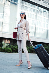 On the way to her flight. Full length of beautiful young woman in sunglasses looking away with smile while pulling her luggage outdoors.