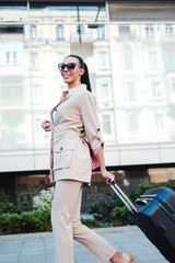 Where I can get a taxi? Side view of beautiful young woman in sunglasses looking away with smile while pulling her luggage outdoors.