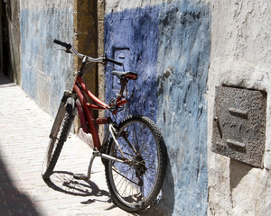 Old bike in a patch of sunlight, leaning against an Alley wall of the Medina