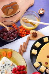 Cheese with mold, fruit, hard cheese with holes on a dark blue background, cheese on a black plate, fruits, nuts, honey, jam, Christmas dinner