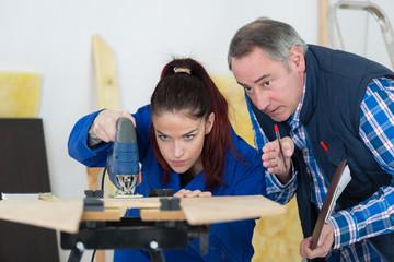 carpenter with female apprentice cutting wood in workshop