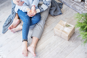 New Year and Christmas 2018. Young couple, gifts, legs, kiss.