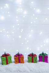 Christmas presents boxes decorations in snow with lights bokeh in background