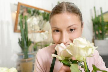 Florist smelling white roses