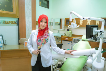 Pretty muslim woman dentist from Indonesia pose in her clinic