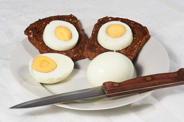 Eggs and two pieces of rye bread on the white plate
