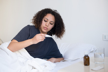 Sick woman checking the result of thermometer