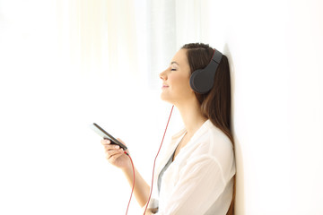 Woman relaxing listening to music isolated at side