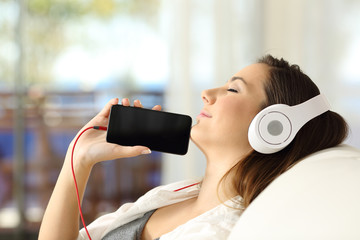 Girl resting listening music and showing phone screen