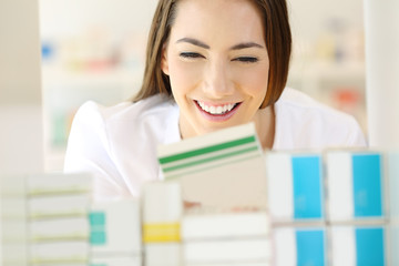 Happy pharmacist finding medicine in a pharmacy