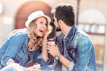 Beautiful young couple enjoying the sun with coffee to go.