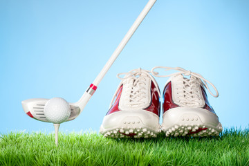 Series of golfing equipment concept pictures..Shot in studio on grass with blue background: Gold Shoes, Ball on Tee and Club