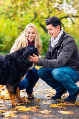 Couple with dog enjoying autumn or fall in nature