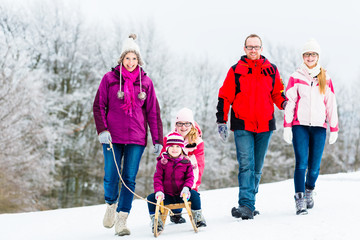Family with kids having winter walk in snow with fun