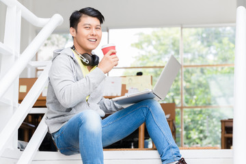 Happy young Asian employee drinking coffee while using a laptop in the interior of a modern office