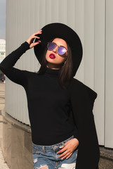 Street shot of gorgeous brunette woman in trendy apparel, wears hat and glasses, posing in sun light
