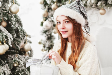 Young beautiful happy smiling girl sitting near the christmas tree, holding gift box. Model wearing stylish white knitted sweater, hat. Winter holidays concept