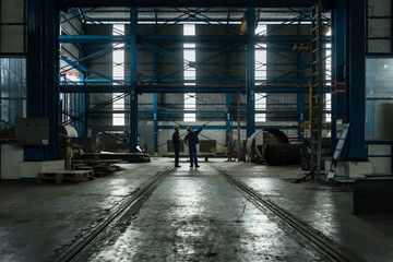 Two workers planning manufacturing process in the interior of an industrial hall