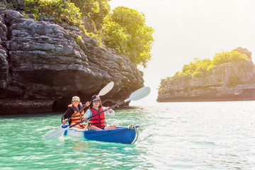 Two women are mother and daughter. Travel by boat with a kayak on the sea under sunlight at summer around Ko Phi, view beautiful nature of the sea, Mu Ko Ang Thong National Park, Surat Thani, Thailand