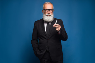 Bearded business man smoking electronic cigarette in the suit. New technology of healthy smoking of electronic vaping cigarette.