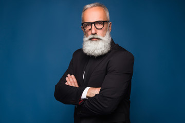 Close-up shot of handsome bearded man in fashion black glasses standing with arms folded isolated on a blue background