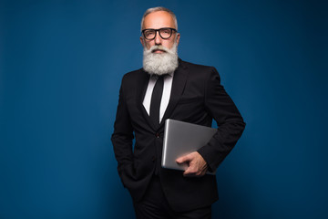 Concentrate bearded senior and business man staying with notebook and working isolated on a blue background. Working business man in straight suit and glasses