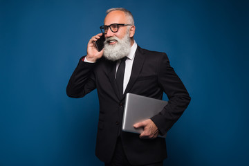 Busy bearded senior and business man staying with notebook and mobile phone isolated on a blue background. Working business man talk on the phone in straight suit and glasses