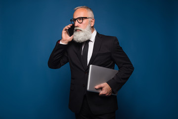 Busy bearded serious senior and business man staying with notebook and mobile phone isolated on a blue background. Working business man talk on the phone in straight suit and glasses.