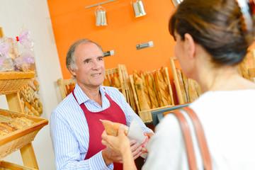 baker handling bread to customer