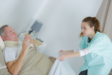 nurse putting a blanket on the patient