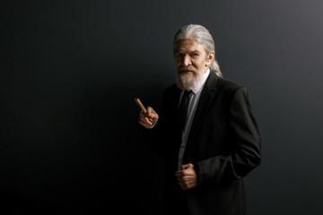 Elrderly stylish man in black jacket holding cigar. Old male portrait in studio on black background.