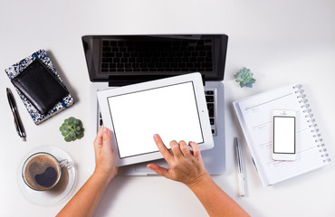 Styled workspace with laptop, phone and and hand holding tablet, flat lay top view scene