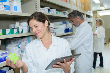 attractive young female pharmacist checking medication