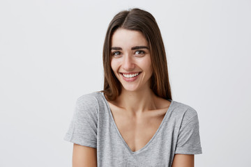 Close up portrait of young cheerful beautiful caucasian girl with dark long hair in casual gray shirt smiling with teeth, looking in camera with happy and relaxed face expression, posing for