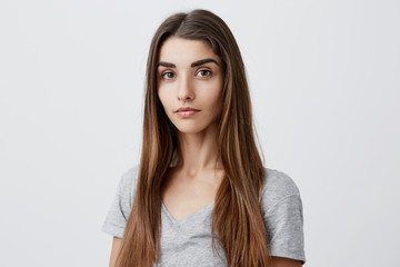 Close up portrait of beautiful serious dark-haired caucasian woman with long hairstyle in casual gray shirt looking in camera with relaxed and calm face expression. Health and beauty.
