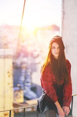 Portrait young handsome long-haired woman on roof in center of city sits a railing at sunset blurred background the urban landscape