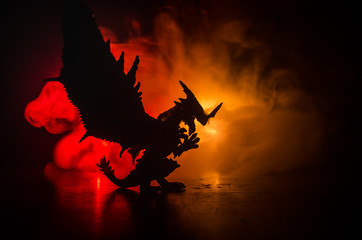 Silhouette of fire breathing dragon with big wings on a dark orange background. Empty space