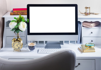 Styled feminine work desk with computer and chair, copy space on screen