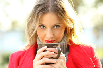 Sensual woman looking at camera with coffee cup