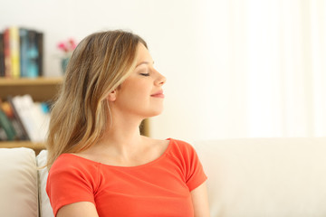 Woman relaxing with closed eyes at home