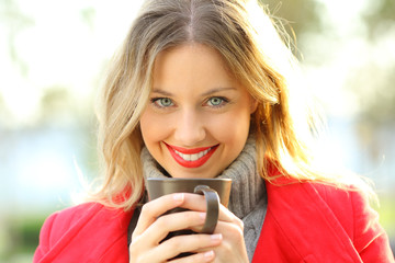 Woman looking at you holding a cup of coffee in winter