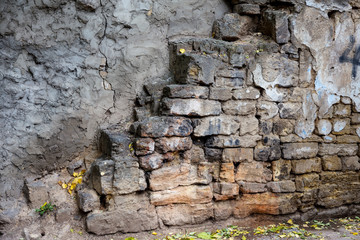 An old destroyed wall with large large cracks. Background of crack on an old wall as background for creative design. Destroyed cracked wall of building after earthquake and hurricane