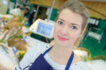 portrait of positive female shop assistant selling fresh fish