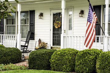 white colonial home decorated for fall with American flag flying from the front porch with rocking chairs