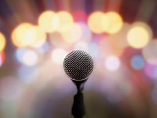 Microphone voice speaker on stage with blurred bright light background