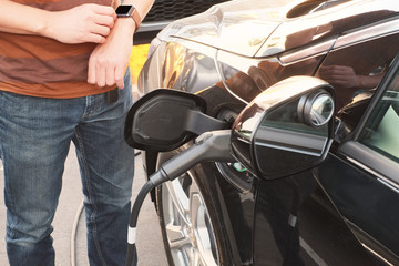 man use smart watch and changing electric car . the modern transportation  technology life.