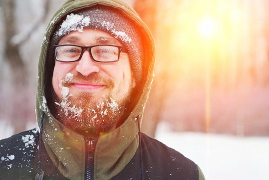 Closeup portrait of happy young bearded man in cold weather the winter forest at sunset. Fun guy smiles. Face, beard , mustache, and glasses misted, covered with frost.